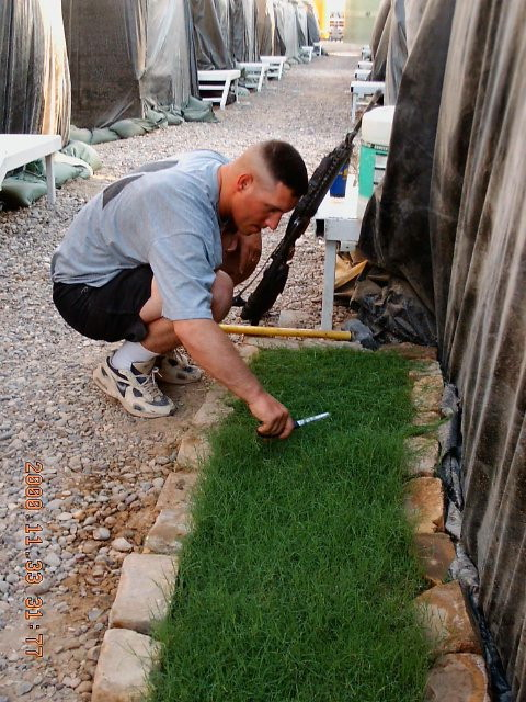 in-july-2004-army-warrant-officer-brook-turner-the-camp-cook-trims-his-grass-with-scissors-in-a-camp-north-of-baghdad-iraq.jpg